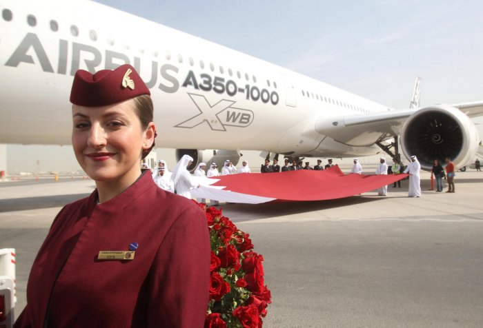 A Qatar Airways flight attendant is seen next to an Airbus A350-1000 in Doha in this file photo.