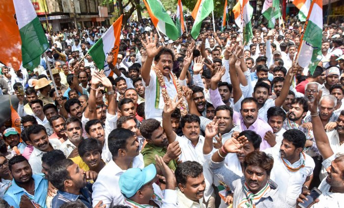 MLA M K Somashekar, Congress candidate of Krishnaraja Assembly segment, waves at his supporters during a procession in Mysuru on Monday.