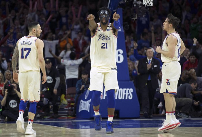 Philadelphia 76ers center Joel Embiid (21) reacts along side guard JJ Redick (17) and guard T.J. McConnell (12) after scoring against the Miami Heat during the fourth quarter in game five of the first round of the 2018 NBA Playoffs at Wells Fargo Center.