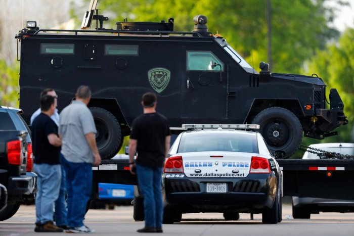 People watch as the Texas Department of Public Safety rolls in heavy duty vehicles to the Home Depot parking lot after two police officers and a civilian were shot by a man outside the home improvement store, on Tuesday in Dallas. AP/PTI