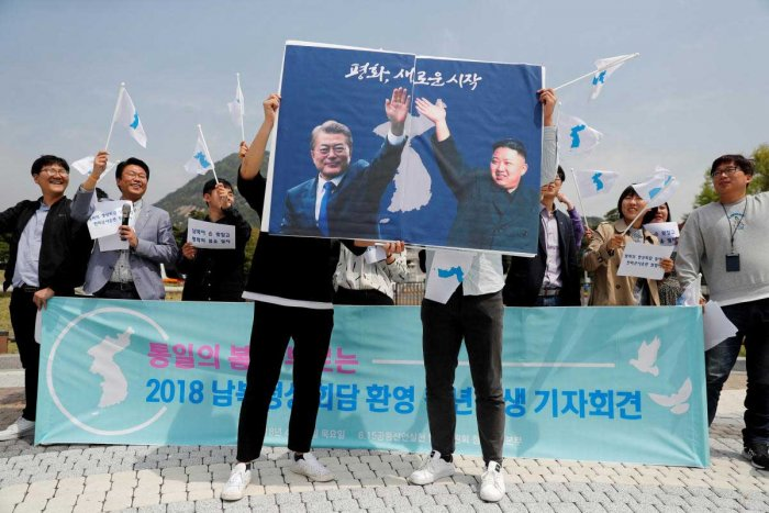 Students hold posters with pictures of South Korea's President Moon Jae-in and North Korea's leader Kim Jong Un during a pro-unification rally ahead of the upcoming summit between North and South Korea in Seoul, South Korea. REUTERS File