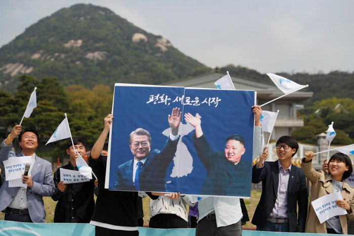 Students hold posters with pictures of South Korea's President Moon Jae-in and North Korea's leader Kim Jong Un during a pro-unification rally ahead of the upcoming summit between North and South Korea in Seoul, South Korea April 26, 2018.
