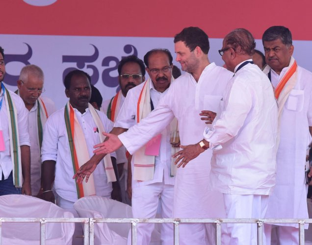 AICC President Rahul Gandhi offering a seat to Veteran Congress leader Janardhan Poojary, during his arrival at the stage, in Bantwal.