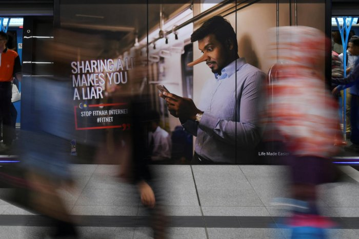 Commuters walk past an advertisement discouraging the dissemination of fake news at a train station in Kuala Lumpur, Malaysia. REUTERS File Photo