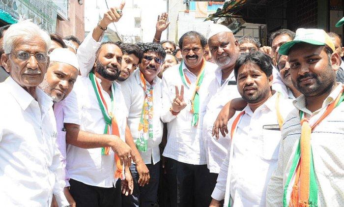 Congress candidate Akhanda Srinivasa Murty with his supporters at D G Halli ward in Bengaluru on Saturday.