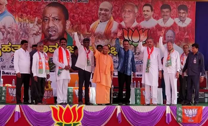 Uttar Pradesh Chief Minister Yogi Adityanath waves hand at crowd when he arrived on the stage for campaigning for the BJP at Vikasashram grounds in Sirsi on Thursday. DH Photo