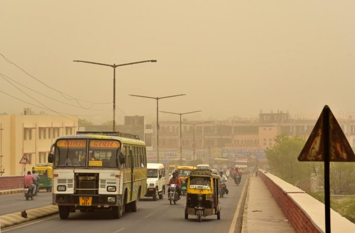 Vehicles ply on roads during a mild dust storm in Bikaner on Thursday. PTI