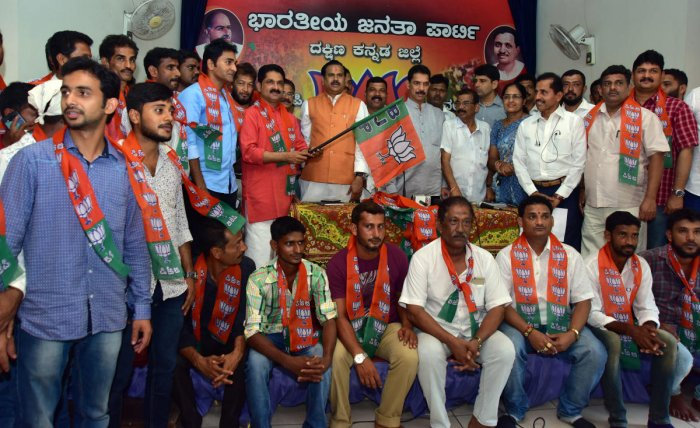 M P Nalin Kumar and Uttar Pradesh Rural Development Minister Dr Mahendra Singh Choudhary welcome Shashiraj Shetty and others to BJP by handing over party flags to them, at the district BJP office in Mangaluru on Thursday. DH Photo