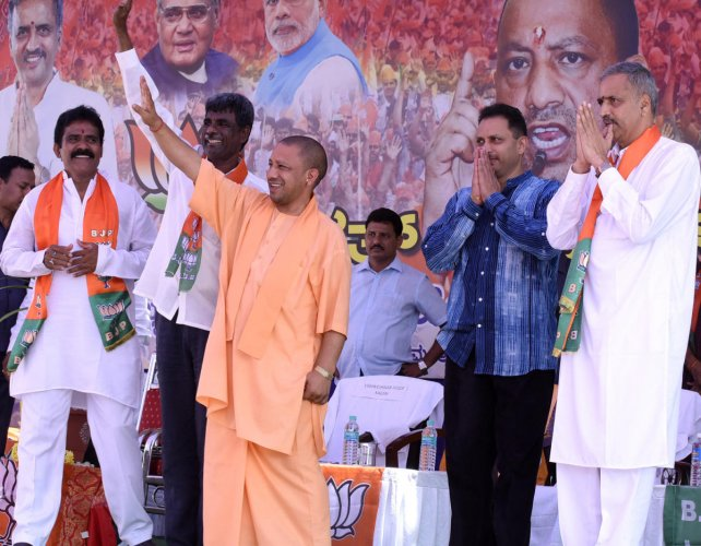 Uttar Pradesh Chief Minister Yogi Adityanath waves to the crowd at a rally at Sirsi, Uttara Kannada district on Thursday. Former minister Kota Srinivasa Poojary, Union Minister Anantkumar Hegde and party candidate Vishveshwar Hegde Kageri look on. dh phot