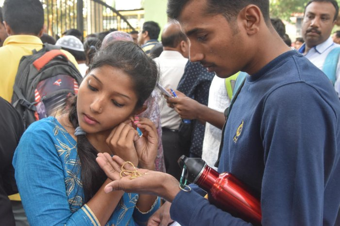A student removes her jewellery before entering the hall for the National Eligibility Cum Entrance Test at an exam centre in the city on Sunday. DH Photo