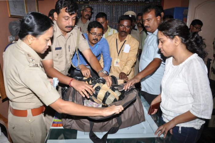 SP Divya Gopinath inspects a bag containing Rs 2.98 crore unaccounted cash seized from a private bus near Kythasandra during wee hours of Monday. DH Photo