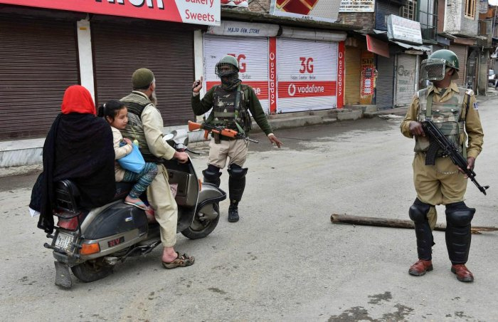 Security personnel stop a motorist during curfew-like restrictions in Srinagar on Monday. PTI