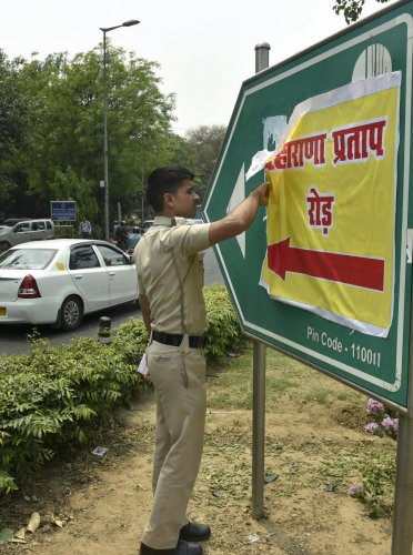 A Delhi policeman removes a poster bearing the name of Maharana Pratap that was pasted on Akbar Road signboard, in central Delhi, on Wednesday. PTI