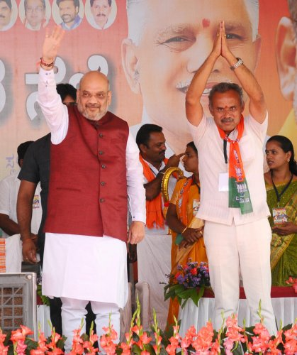 BJP national president Amit Shah, party candidate from Tumakuru Rural B Suresh Gowda wave at the crowd during an election rally at Hebburu in Tumakuru taluk on Wednesday. DH PHOTO