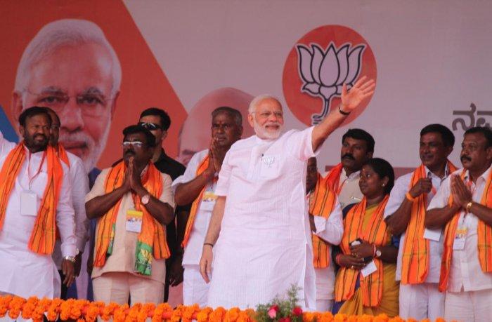 Prime Minister Narendra Modi waves at people at an election campaign at Beerandahalli in Bangarpet taluk in Kolar district. DH photo