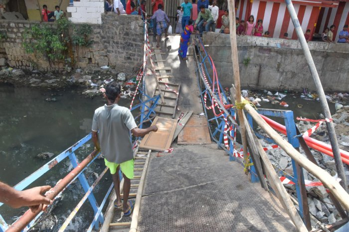 Metal foot bridge is clopped during a party workers going on for assembly election campaign on Tuesday, at ISRO colony, Cambridge layout, Sai Baba Temple road, Halasuru in Bengaluru on Wednesday. Photo by S K Dinesh