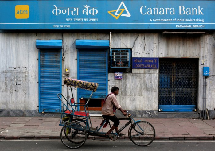 FILE PHOTO - A rickshaw puller passes the Canara Bank branch in the old quarters of Delhi, India, September 6, 2017. REUTERS