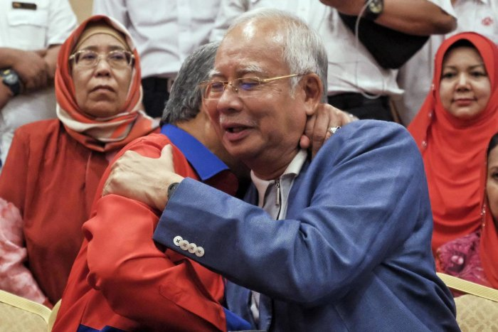 Former Malaysian Prime Minister Najib Razak, right, hugs former deputy Prime Minister Ahmad Zahid Hamidi, left, during a press conference in Kuala Lumpur, Malaysia, Saturday, May 12, 2018. Najib Razak says he's resigning as head of his Malay party to take