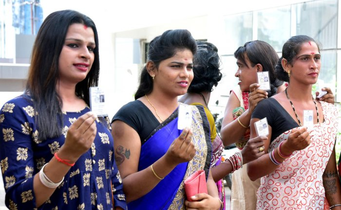 Transgenders display their voter IDs outside a polling booth in Mangaluru on Saturday.