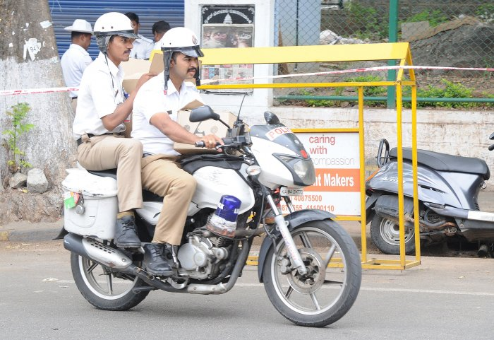 Not strapping helmets or improper use of helmets is a common sight in the city, even among police officials. DH PHOTO BY SRIKANTA SHARMA R