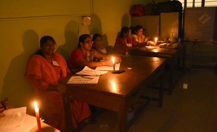 As power supply was severely affected in some parts of the city and rural areas, poll staff at Government Training Centre at Gandhi Nagar working under candle light.