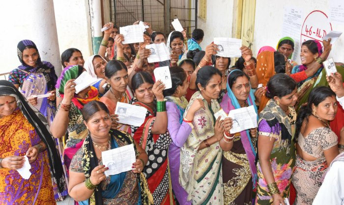 Women stand in Queue to exercise their franchise for Assembly Election at Korahalli village in Aland taluk in Kalaburagi District on Saturday.