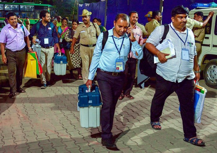 Officials arrive to hand over the EVM and VVPAT machines after the end of voting for Assembly elections, in Bengaluru on Saturday. PTI Photo