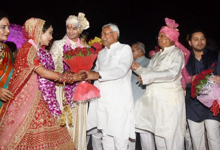Bihar Chief Minister Nitish Kumar greets RJD chief Lalu Prasad Yadav's latter's elder son Tej Pratap during the wedding ceremony at Veterinary College Ground in Patna on Saturday. PTI Photo