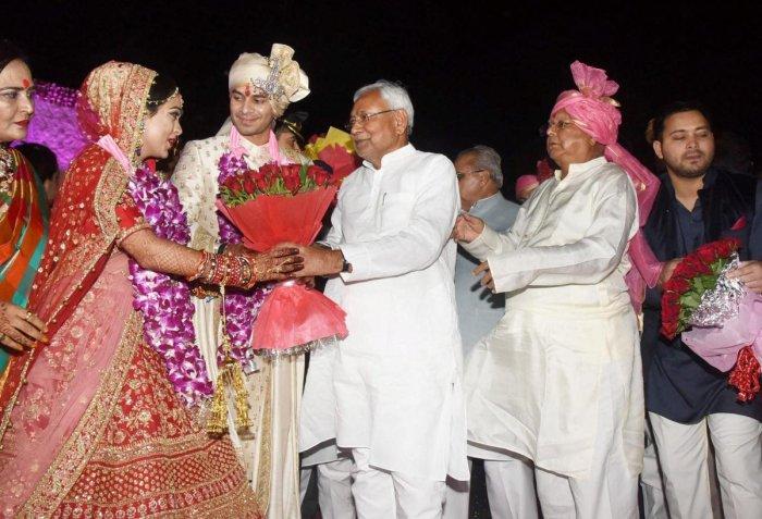 Bihar Chief Minister Nitish Kumar greets RJD chief Lalu Prasad Yadav's latter's elder son Tej Pratap during the wedding ceremony at Veterinary College Ground in Patna on Saturday. PTI Photo
