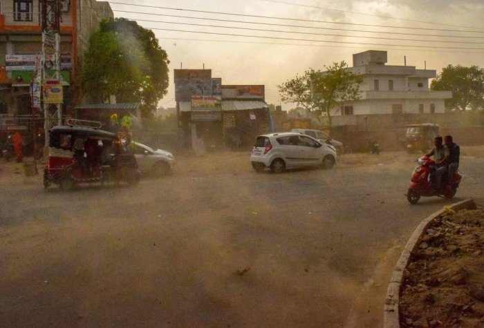 Vehicles ride past during a dust storm in Mathura on Wednesday. PTI file Photo