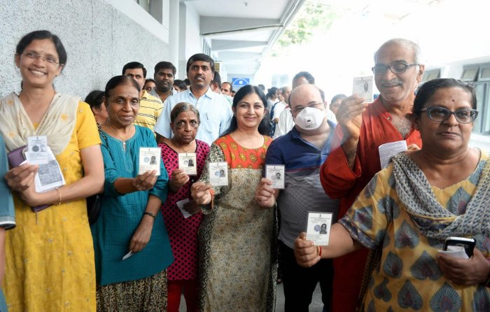 Voters show their Election Commission IDs before they cast their ballot during the polling day for the Karnataka Assembly election. PTI photo
