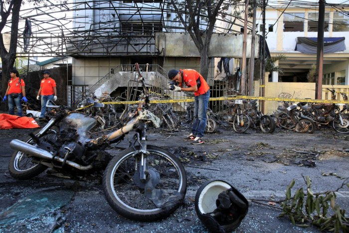 A forensic police officer takes pictures of debris near burned motorcycles following a blast at the Pentecost Church Central Surabaya (GPPS), in Surabaya. Reuters file photo
