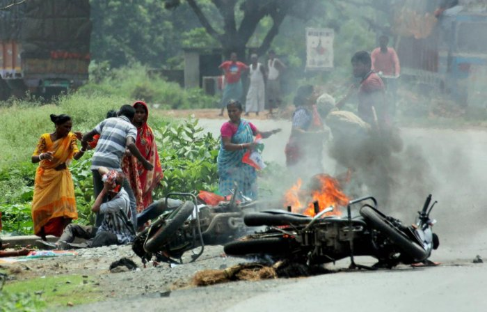 People injured in poll violence sit by the side of a road as a vehicle is set on fire by locals during panchayat polls, in Nadia district of West Bengal on Monday. PTI