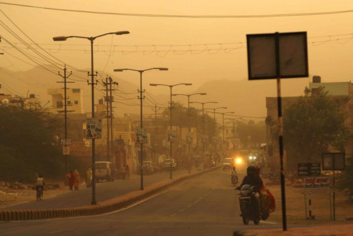Commuters travel along a road during a heavy dust storm in Ajmer, Rajasthan, on Monday. AFP