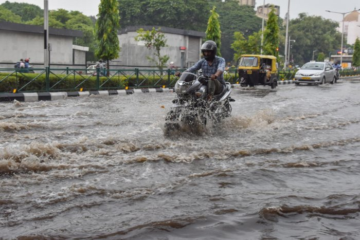 Motorist struggle to ride vehicles in stagnanted Rain water opp Cubbon Park Metro station, Cubbon Road in Bengaluru on Monday. Photo by S K Dinesh