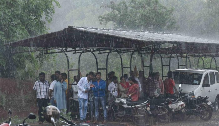 People take shelter under a two-wheeler parking stand in Dharwad after skies opened up on Wednesday evening. DH PHOTO