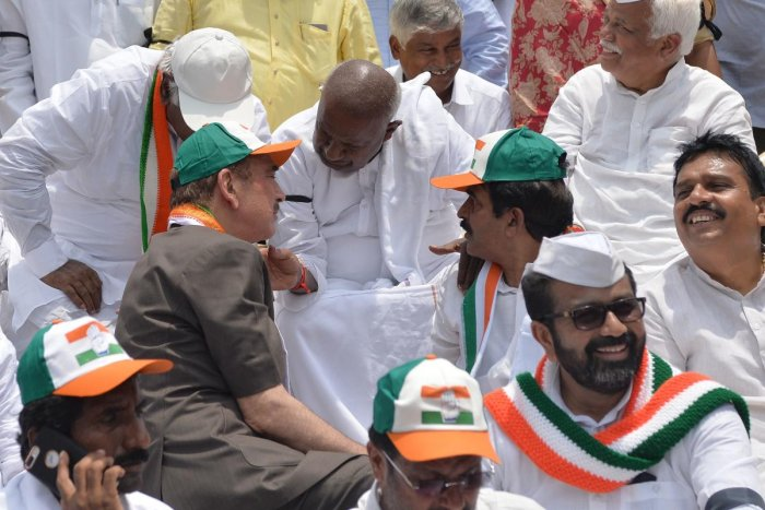 Janatha Dal (Secular) national president, H.D. Deve Gowda (C), speaks with Congress leader Ghulam Nabi Azad (L) as they stage a dharna in front of the Gandhi Statue against the Karnataka Governor's order to invite Bharatiya Janatha Party Legislative Party