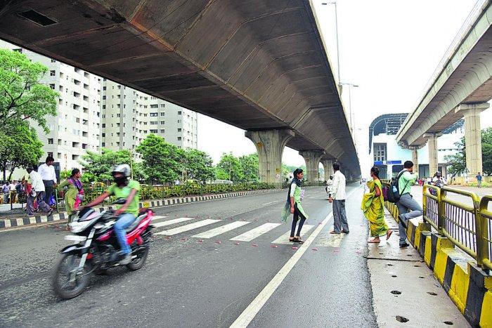 Pedestrians struggle to cross the road, at Nagasandra Metro Station, in Bengaluru on Thursday. DH Photo/ B H Shivakumar