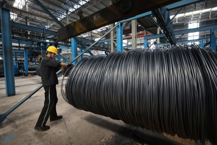 (FILES) This file photo taken on May 1, 2018 shows a worker handling steel cable at a steel factory. AFP