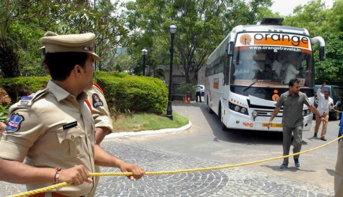 A poiceman looks on as Karnataka Congress and JD(S) MLAs arrive in a bus at Taj Krishna Hotel, in Hyderabad, on Friday. (PTI Photo)