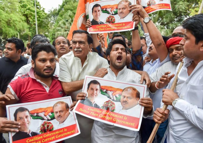Congress party workers celebrate with posters of party President Rahul Gandhi and JD(S) chief HD Kumarswamy after Karnataka Chief Minister BS Yeddyurappa announced his resignation, in New Delhi on Saturday. PTI Photo