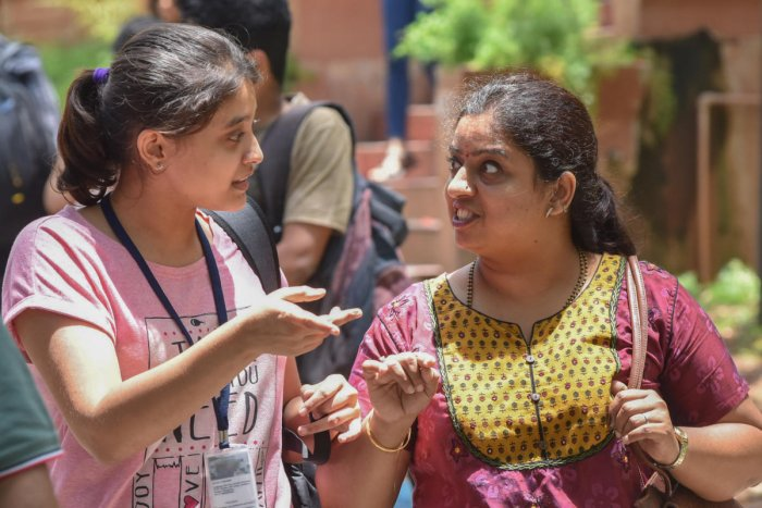 A student seen discussing the exam paper with her mother at the Dayananda Sagar College on Sunday. DH Photo/S K Dinesh