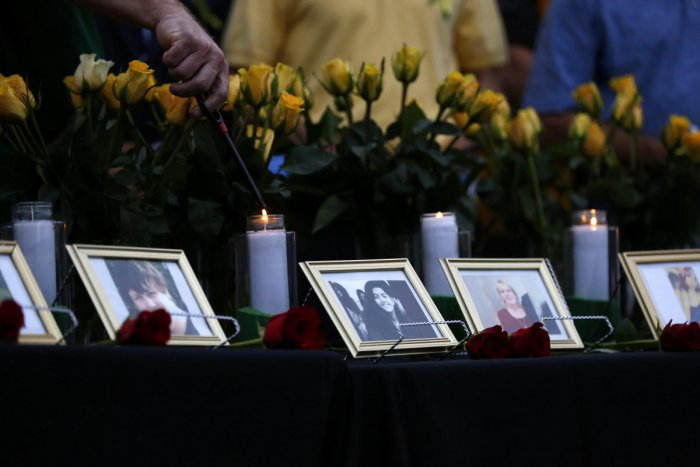 Candles are lit behind images of the victims killed in a shooting at Santa Fe High School during a vigil in League City, Texas, U.S., May 20, 2018. (REUTERS)