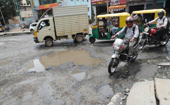 Huge potholes on the 89 Feet Road of Hosakerehalli Cross at Banashankari on Monday. DH Photo/Srikanta Sharma R.
