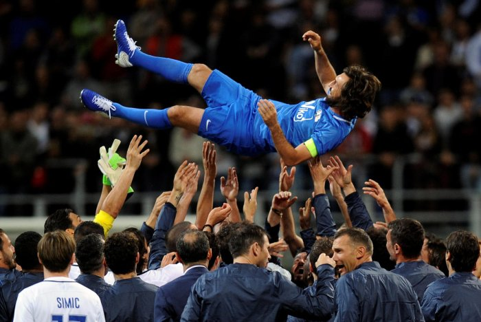 BIDDING GOODBYE Former Italian legend Andrea Pirlo is lifted up at the end his farewell match at the San Siro stadium in Milan on Monday. Reuters