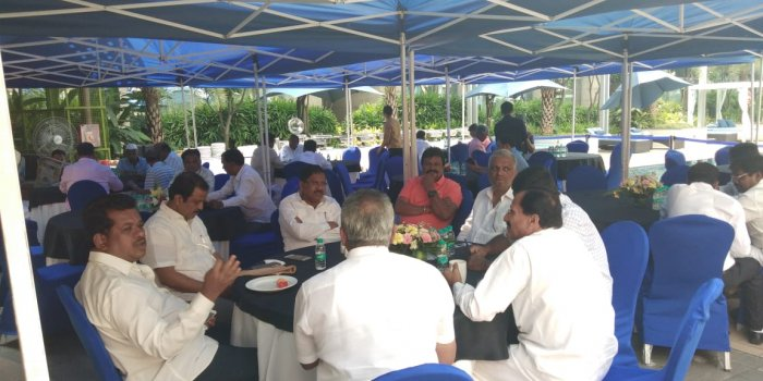 Congress leaders chat over breakfast by the poolside at the Hilton on Tuesday.