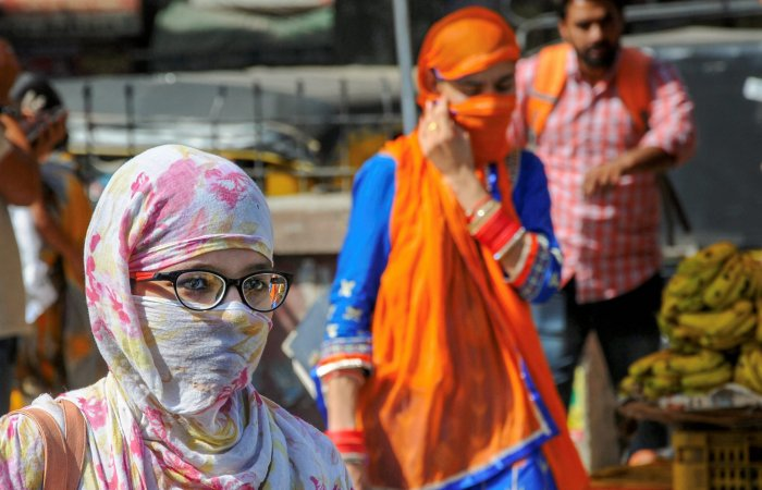 People shield themselves against direct heat on a hot, summer day, as temperature soars, in Amritsar, on Wednesday. PTI