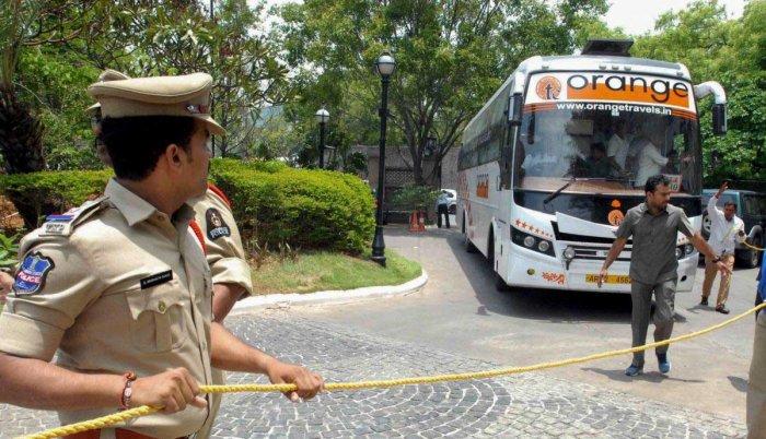A poiceman looks on as Karnataka Congress and JD(S) MLAs arrive in a bus at Taj Krishna Hotel, in Hyderabad. PTI file photo