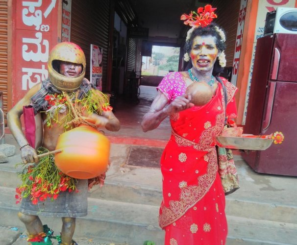 Tribals dress up in weird costumes to celebrate 'kunde habba' on Devarapura temple premises near Titimathi, Gonikoppa, Kodagu district.