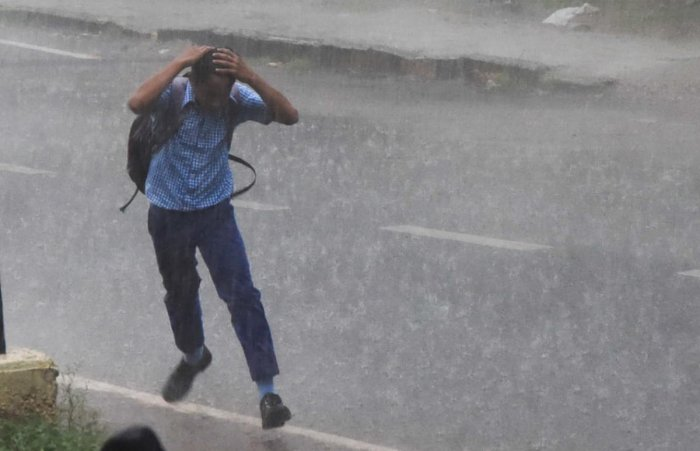 A boy running during sudden rain at Ramavilas Road in Mysuru on Friday. -Photo by Savitha. B R
